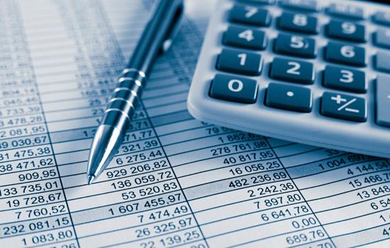 Kalkulator i długopis na kosztorysie usługi księgowe
